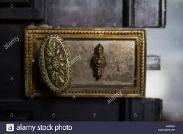 front view detail closeup of old vine golden handle door lock with metallic inlay on black wooden background