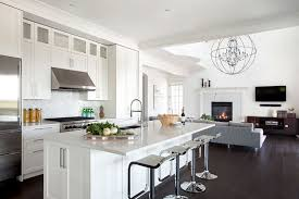 open concept kitchen with white cabinets accented with nickel hardware alongside sleek white quartz countertops with a marble herringbone tiled backsplash