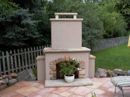 stucco and stone gas outdoor fireplace in greeley landscape