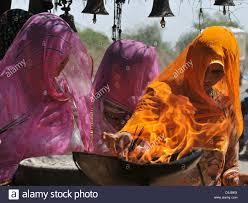 stock photo three tribal women lighting incense sticks from fire bowl tribal woman praying at alter aravalli hills rajasthan india alter lighting