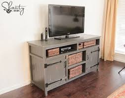 a distressed gray tv stand in a farmhouse style