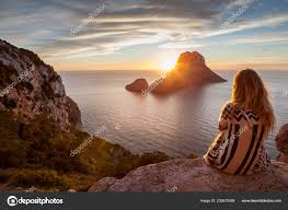 woman back to the front watching a beautiful sunset at the beach the beach is called es vedra in ibiza and belongs to balearic islands in spain photo