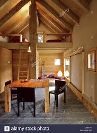 interior of chalet with dining table and sleeping loft, stone floor and  wood paneling