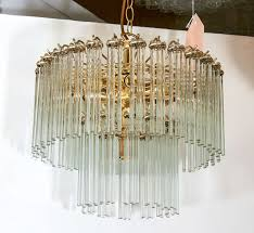 a vintage two tier chandelier with thin glass rods suspended from a brass frame
