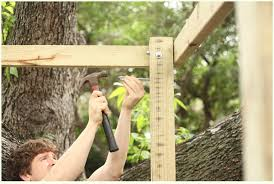 Man hammering an eye bolt into the frame of a hanging bed