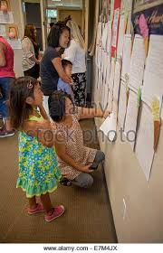 asian american family mom dad father stock photos asian american  asian american mothers look over their children s essay writing posted on a classroom wall on parents