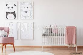 pink chair near cradle with blanket in white baby s room interior with posters and rug