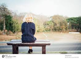 women sitting alone on a bench waiting