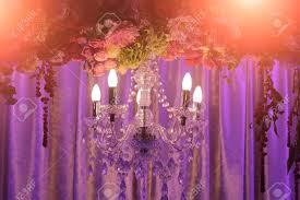 photo closeup of one classic cut glass crystal chandelier lighting fixture with electric opal bulbs