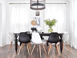 contemporary dining room features a metal mesh drum chandelier illuminating a dark stained rectangular dining table lined with a mix of black and white