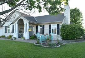 White brick home with black shutters and a turquoise blue front door completed with chippendale lattice portico. Adding Curb Appeal How To Paint Shutters And Front Door Our House Now A Home
