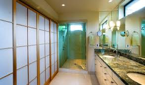 a remodeled bathroom with a green granite countertop and two sinks