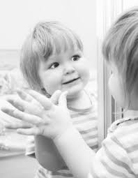 toddler looking in mirror. a girl looks in the mirror. black and white image of baby. toddler looking mirror