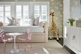 beautifully designed pink and gold toddler s bedroom features a saarinen accent table seating two lou lou ghost chairs on a beige greek key rug in front of