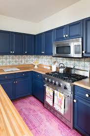 a bold blue kitchen with light colored wooden countertops and a mosaic tile backsplash