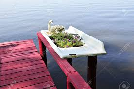 old kitchen or bathroom sink turned into a planter by a lake stock