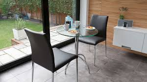small round glass dining table and faux leather dining chairs