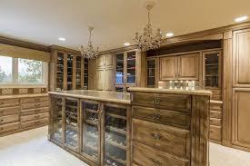 big luxury walk in closet with 2 chandeliers center island with shoe rack dresser