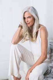 Faux fur elegant long grey hair older women white clothes.