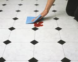 wiping tomato ketchup off a tiled floor close up high angle view