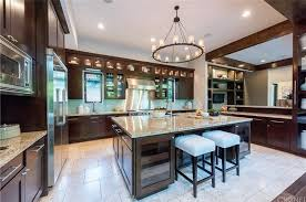 chandelier and recessed lights makes the white walls and countertops of kitchen glow