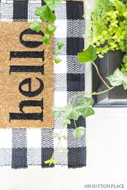 hello doormat on black and white buffalo check rug on porch