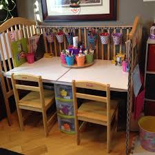 we upcycled our old drop side crib into an art desk along with a homemade carousel for markers and such