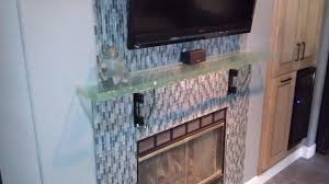interior transpa glass mantel shelf with black led tv and brown metal fire box of