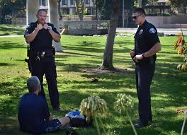 officers brian hatfield left and bryan meers talk to a veteran outside the garden grove regional library across the street from garden grove high