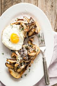 healthy mushroom breakfast toast with a pan fried egg and parmesan cheese