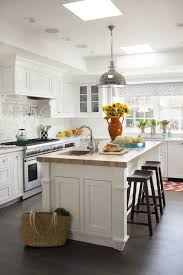beautiful kitchen features island topped with maple butcher block countertop and prep sink lined with espresso sawhorse barstools illuminated by restoration