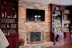 chicago faux stone fireplace family room traditional with tv over wooden mantels and