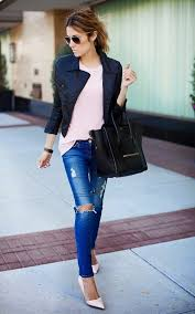 classic black leather jacket is worn atop pastel pink loose fit top half tucked in blue ripped slim jeans completed with pale pink pointed toe pumps
