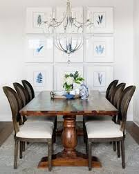 french cane back dining chairs sit on a gray and blue rug and flank a wood trestle dining table illuminated by a silver scroll chandelier hung in front of a