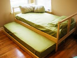 amazing ikea trundle beds with cream color wooden trundle bed frames and green color covered bedding sheets pillows