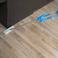 applying polyurethane to hardwood flooring with a stain pad