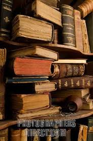 very old and dusty books spine in a heap on a bookshelf stock photo