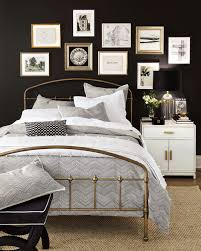 bedroom with black walls white bedding and a gallery wall over the bed