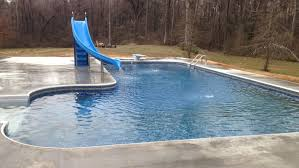 l shaped swimming pool with a slide and diving board