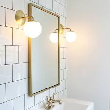 white square tile with black grout brass sconces and plumbing fixtures