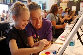 emily nelson 6 gets help from her mom candice nelson painting a unicorn at