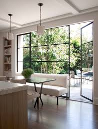 View in gallery Eating area in a kitchen with floor-to-ceiling windows