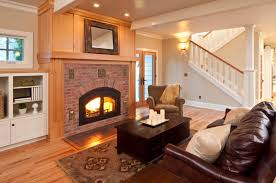 a living room off of the foyer with a large wooden and brick mantle around the