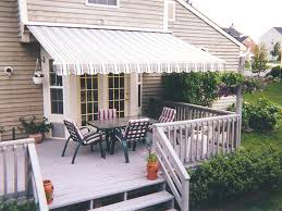 striped awning over double doors with outdoor chairs and table on a deck motorized awnings for decks e73