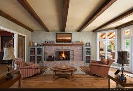 The large red brick fireplace is the centerpiece of this rustic living  room. Natural hardwood