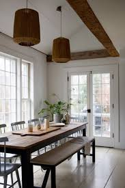 above in the lofty dining room a long table designed and built by percy himself sits under two bungalow pendant lights from anthropologie 198 each