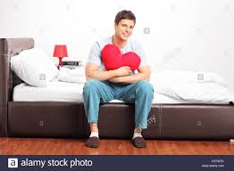 Man Shaped Pillow Young Man Sitting On A Bed And Holding A Heart Shaped Pillow Stock