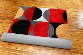 brightly colored black red grey yellow and white area rug partially unrolled