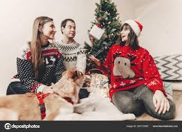 merry christmas and happy new year concept stylish hipster family in festive sweaters with cute dog tossing up gift at christmas tree lights happy