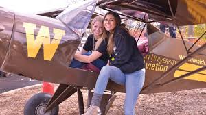 family engagement western michigan university students posing in front of an airplane